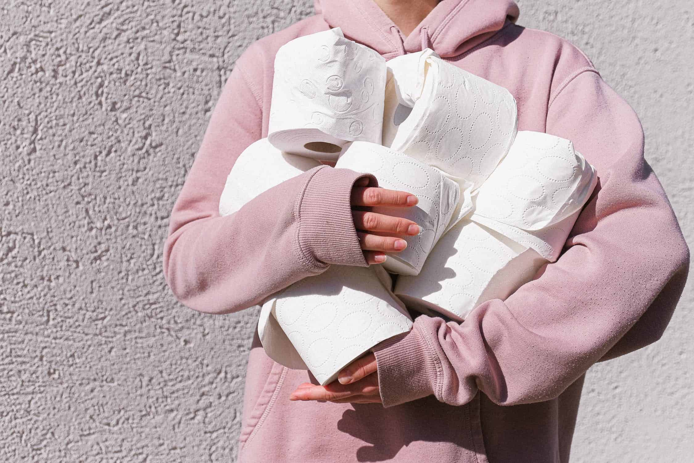 Person in a pink sweater grasping toilet paper rolls.